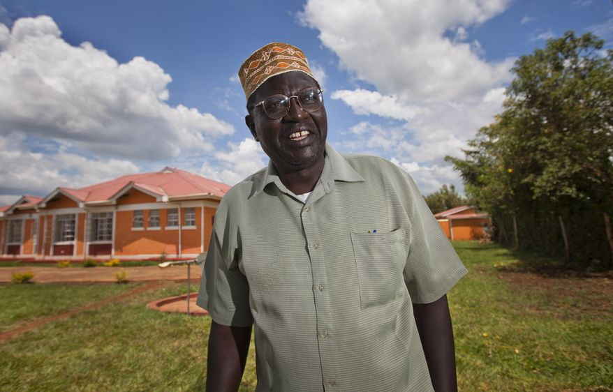 Malik Obama, half brother of U.S. President Obama, poses for photographs after speaking about the upcoming U.S. elections in the village of Kogelo, Kenya, on Sunday, Nov. 4, 2012. He predicted the president would win re-election. (AP Photo/Ben Curtis)