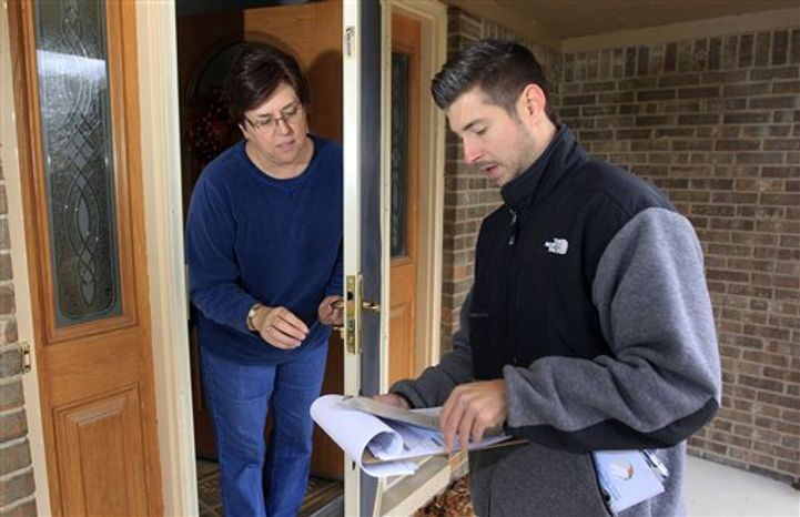 In a photo from Thursday, Nov. 1, 2012, David Herbeck prepares to give Katherine Davenport some campaign literature as he walks door-to-door in a Livonia, Mich., suburb reminding voters to vote on Tuesday. (AP Photo/Carlos Osorio)