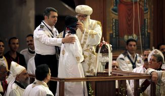 Acting Coptic Pope Pachomios (center) blindfolds the boy elected to draw the name of the next patriarch from a crystal chalice during an elaborate papal election ceremony at the Coptic cathedral in Cairo on Sunday, Nov. 4, 2012. (AP Photo/Nasser Nasser)