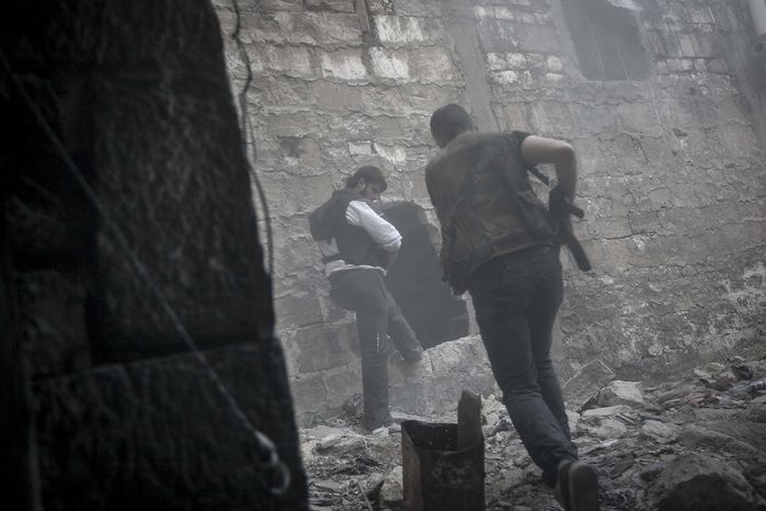 Rebel fighters run for cover through smoke from an explosion as they try to repel a coordinated attack from mortar, tank and aerial artillery fire by loyalists of President Bashar Assad in the Jedida district of Aleppo, Syria, on Saturday, Nov. 3, 2012. (AP Photo/Narciso Contreras)