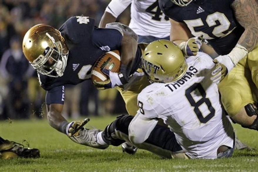 Notre Dame running back Theo Riddick drives to the one-yard line as he is tackled by Pittsburgh linebacker Todd Thomas during the third overtime period in an NCAA college football game in South Bend, Ind., Saturday, Nov. 3, 2012. Notre Dame defeated Pittsburgh 29-26 in triple overtime. (AP Photo/Michael Conroy)