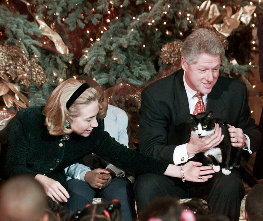 "President Clinton holds Socks the cat as he and Mrs. Clinton hosted Washington area elementary school children at the White House Friday Dec. 20, 1996 where the president read ""Twas the Night Before Christmas."" (AP Photo/Ruth Fremson)"