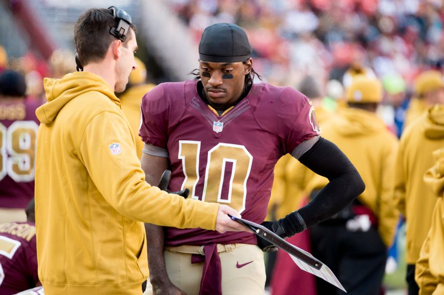 Washington Redskins offensive coordinator Kyle Shanahan talks with Washington Redskins quarterback Robert Griffin III (10) on the sideline after a three and out offensive series in the fourth quarter as the Washington Redskins take on the Carolina Panthers at FedEx Field, Landover, Md., Sunday, November 4, 2012. (Andrew Harnik/The Washington Times)