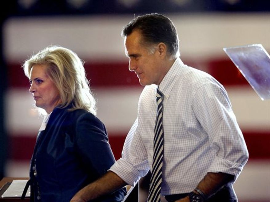 Former Massachusetts Gov. Mitt Romney (right), the Republican presidential candidate, steps offstage with his wife, Ann, after a speech at a campaign event at the International Exposition Center in Cleveland on Sunday, Nov. 4, 2012. (AP Photo/David Goldman)