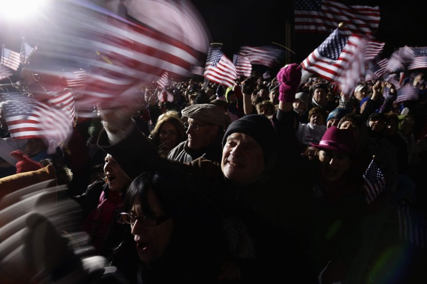 Supporters wave flags as Republican presidential candidate and former Massachusetts Gov. Mitt Romney speaks at a Pennsylvania campaign rally at Shady Brook Farm, in Morrisville, Pa., Sunday, Nov. 4, 2012. (AP Photo/Charles Dharapak)