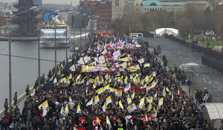 Ultranationalist demonstrators and activists march carrying the Russian Empire's black, yellow and white flag to mark National Unity Day, on the outskirts of Moscow on Sunday, Nov. 4, 2012. (AP Photo/Ivan Sekretarev)