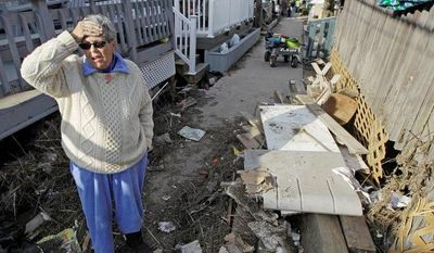 Ginny Flanagan, 70, who lives in Breezy Point, returns to her damaged home and destroyed neighborhood for the first time in the wake of Superstorm Sandy, Sunday, Nov. 4, 2012, in New York.  (AP Photo/Kathy Willens)