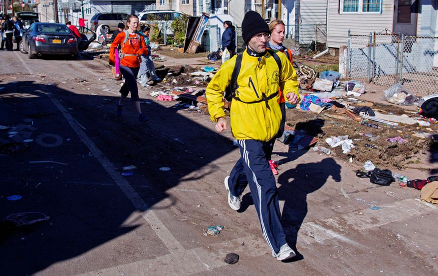 Carrying a backpack with goods and supplies, marathon runner Eitan Tabak runs past debris in the hard hit Midland Beach neighborhood of the Staten Island borough of New York, Sunday, Nov. 4, 2012. Background right is marathon runner Michelle Mascioli and far left marathon runner Rachel Wheeler of New York. With the cancellation of the New York Marathon, hundreds of  runners, wearing their marathon shirts and backpacks full of supplies, took the ferry to hard-hit Staten Island and ran to neighborhoods hard hit by Superstorm Sandy to help. (AP Photo/Craig Ruttle)