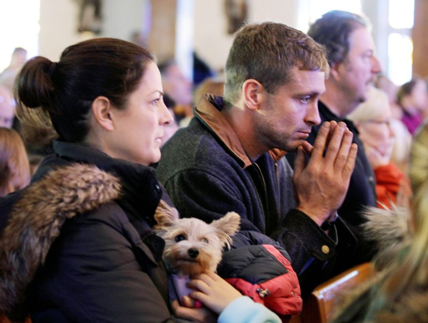 "Meg Dolan holds her dog ""Nellie"" during Sunday mass at St. Thomas More Catholic Church in Breezy Point, in the wake of Superstorm Sandy, Sunday, Nov. 4, 2012, in New York. (AP Photo/Kathy Willens)"