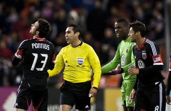 D.C. United midfielder Chris Pontius (13) and goalkeeper Bill Hamid (28) argue the ruling of an own goal by goalkeeper Bill Hamid during the second half against the New York Red Bulls in the Eastern Conference semifinals p