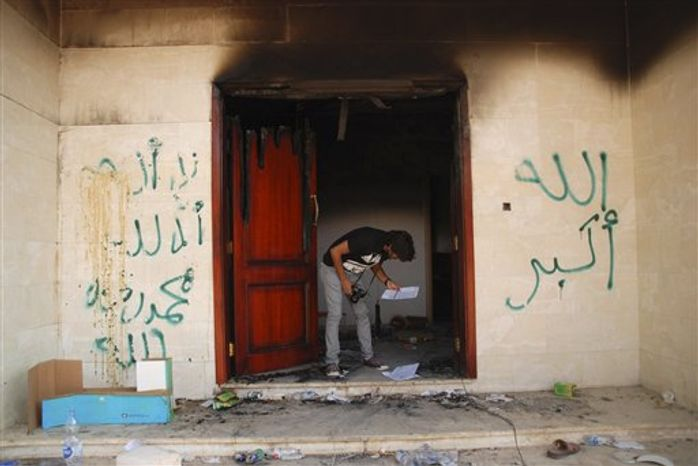 "** FILE ** In this Wednesday, Sept. 12, 2012 photo, a man looks at documents at the U.S. consulate in Benghazi, Libya, after an attack that killed four Americans, including Ambassador Chris Stevens. The graffiti reads, ""no God but God,"" "" God is great,"" and ""Muhammad is the Prophet."" (AP Photo/Ibrahim Alaguri)"