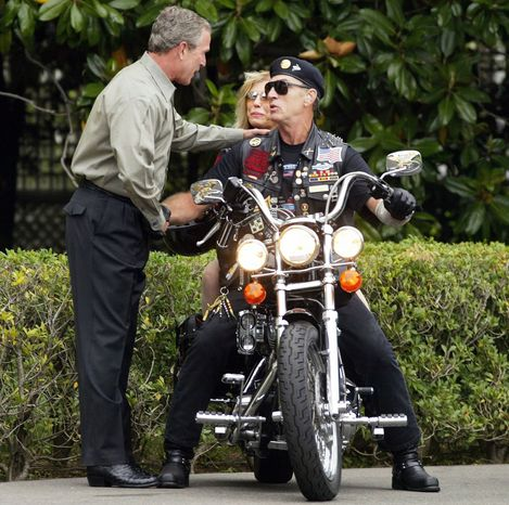 President Bush greets Artie Muller, executive director of Rolling Thunder, and singer Nancy Sinatra at the White House in 2004. The motorcycle group is strongly supporting Mitt Romney for president. (Associated Press)