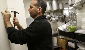 **FILE** Anthony Cavallo, owner of the restaurant Vintage 50, mounts a potato cutter in his restaurant in Leesburg, Va., on Oct. 8, 2012. (Associated Press)