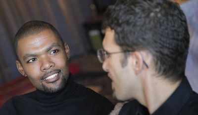 Ludovic-Mohamed Zahed (right), who married his live-in partner, Qiyaammudeen Jantjies, in South Africa, where gay marriage is recognized, is interviewed in Sevran, France, outside Paris, on Monday, Oct. 22, 2012. (AP Photo/Christophe Ena)