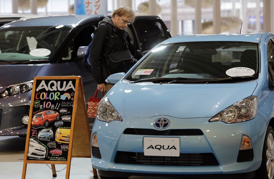 A man inspects an Aqua model at a Toyota Motor Corp. showroom in Tokyo on Monday, Nov. 5, 2012. Toyota's quarterly profit tripled, driven by a recovery from natural disasters, and the company raised its full-year earnings forecast despite a sales slump in China. (AP Photo/Koji Sasahara)