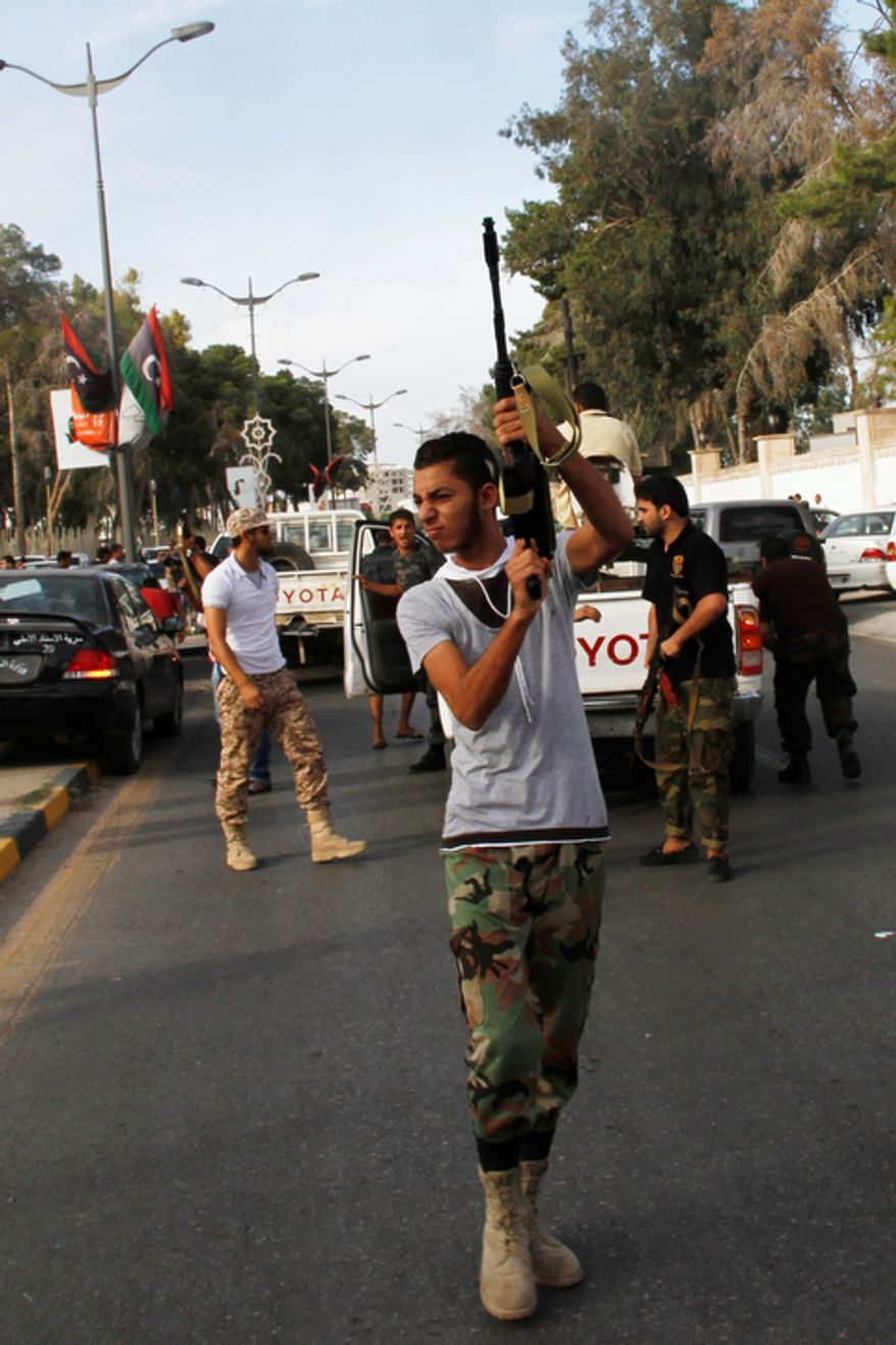 In this Sunday, Oct. 21, 2012, photo, a Libyan militiaman fires his weapon in the air in an attempt to force back protesters from in front of the gates of the parliament in Tripoli, Libya. One year on, the country is still trying to overcome the legacy of Moammar Gadhafi, one of the most erratic leaders of modern times, as well as a brutal eight-month struggle that left Syria awash in weapons, militias and very few viable institutions of state. (AP/Paul Schemm)
