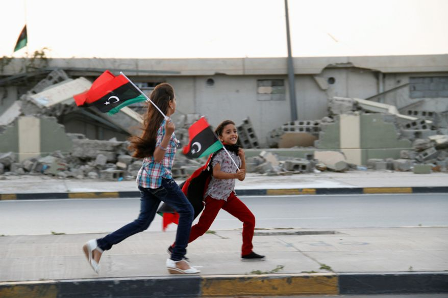 In this Tuesday, Oct. 23, 2012, photo, two Libyan girls run with national flags in front of the destroyed remnants of deposed leader Moammar Gadhafi's once-feared Bab al-Aziziyah compound in Tripoli, Libya, on the anniversary of his fall. One year on, the country is still trying to overcome the legacy of one of the most erratic leaders of modern times as well as a brutal eight-month struggle that left the country awash in weapons, militias and very few viable institutions of state. (AP/Paul Schemm)