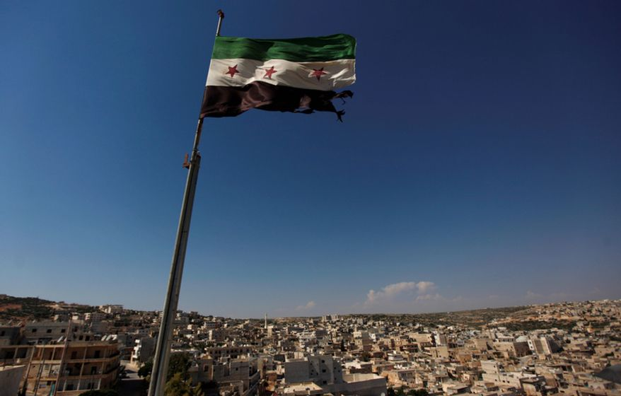 This June 12, 2012, photo shows a Syrian revolutionary flag waving atop a building on the outskirts of Aleppo, Syria. Syria's conflict is the most violent to emerge from last year's Arab Spring. The protests started peacefully but prompted a brutal crackdown by President Bashar Assad's government. The fighting has escalated into a civil war that has killed more than 30,000 people over the last year and a half, according to activists. Despite intervening in Libya, the United States has steered clear of taking military action or arming Syria's rebels. (AP Photo/Khalil Hamra, File)