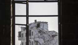 A damaged building is seen through a window on Sunday, Nov. 4, 2012, after several weeks of intense battles between rebel fighters and the Syrian army in the Jedida district of Aleppo, Syria. (AP Photo/Narciso Contreras)