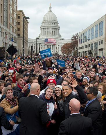With the Wisconsin Capitol dome as a backdrop, President Obama waves to the press as he greets supporters at a campaign event on Monday, Nov. 5, 2012, in downtown Madison, Wis. (AP Photo/Carolyn Kaster)