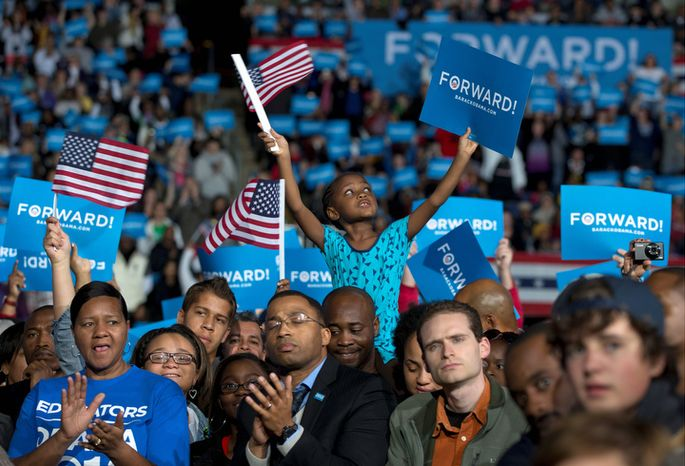 Amara Hayles, 6, of Columbus, sits atop her dad, Marlon Hayles, shoulders and waves a American flag as President Barack Obama speaks at a campaign event at Nationwide Arena, Monday, Nov. 5, 2012, in Columbus, Ohio. (AP Photo/C