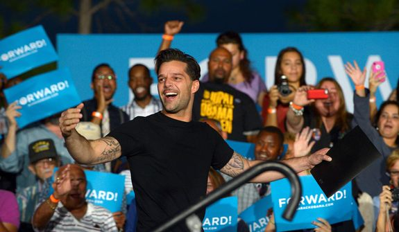 Entertainer Ricky Martin walks onstage to speak before first lady Michelle Obama during a campaign stop for President Barack Obama on election eve in Orlando, Monday, Nov. 5, 2012.(AP Photo/Phelan M. Ebenhack)