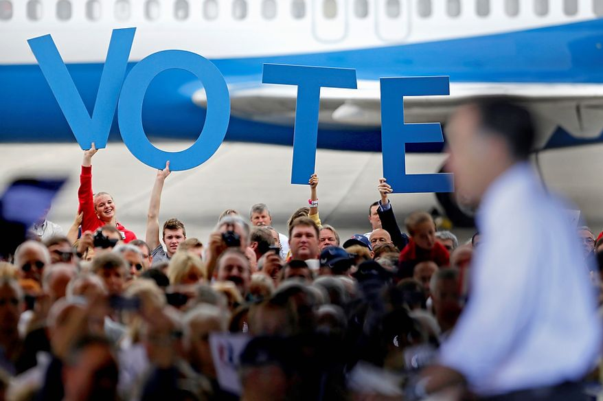 "Crowd members hold up a sign reading ""Vote"" as Republican presidential candidate Mitt Romney speaks during a campaign event at the Orlando Sanford International Airport on Monday, Nov. 5, 2012, in Sanford, Fla. (AP Photo/David Goldman)"