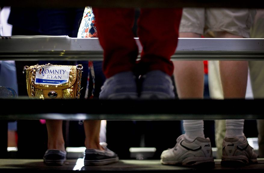 A purse with a Romney-Ryan sticker sits next to suppoters on a bleacher as Republican presidential candidate Mitt Romney speaks at a campaign event at Orlando Sanford International Airport on Monday, Nov. 5, 2012, in Sanford, Fla. (AP Photo/David Goldman)