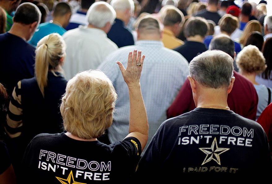Supporters observe a moment of prayer before Republican presidential candidate Mitt Romney speaks at a campaign event at Orlando Sanford International Airport on Monday, Nov. 5, 2012, in Sanford, Fla. (AP Photo/David Goldman)