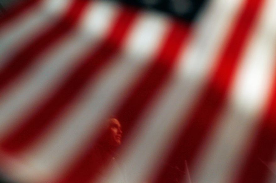 Republican presidential candidate Mitt Romney is seen speaking through a supporter's flag at a campaign rally at Newport News/Williamsburg International Airport in Newport News, Va., on Sunday, Nov. 4, 2012. (AP Photo/Charles Dharapak)