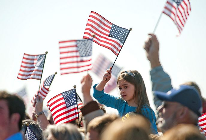 Supporters wave the American flag as Republican presidential candidate, former Massachusetts Gov. Mitt Romney speaks to supporters at a Virginia campaign rally at Lynchburg Regional Airport in Lynchburg, Va., on Monday Nov. 5, 2012. (