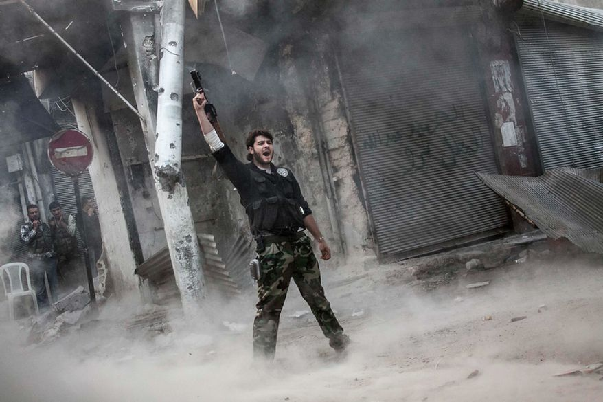 A rebel fighter claims victory Nov. 4, 2012, after launching a shoulder-fired missile toward a building where Syrian troops loyal to President Bashar Assad are hiding while they attempt to gain terrain against the rebels during heavy clashes in the Jedida district of Aleppo, Syria. (Associated Press)