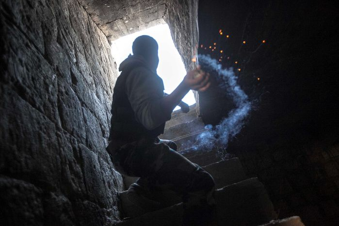 A rebel fighter prepares to throw a homemade grenade Nov. 4, 2012, toward a building where Syrian troops loyal to President Bashar Assad are hiding while they attempt to gain terrain against the rebels during heavy clashes in the Jedida district of Aleppo, Syria. (Associated Press)