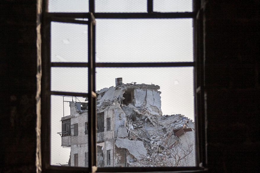 A damaged building in the Jedida district of Aleppo, Syria, is seen Nov. 4, 2012, through a window after several weeks of intense battles between rebel fighters and the Syrian army. (Associated Press)