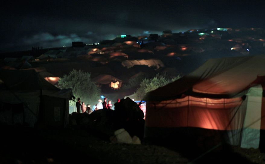 Syrians who fled from the violence in their village walk Nov. 4, 2012, between the tents at a camp for the displaced in the Syrian village of Atma, near the Turkish border with Syria. (Associated Press)