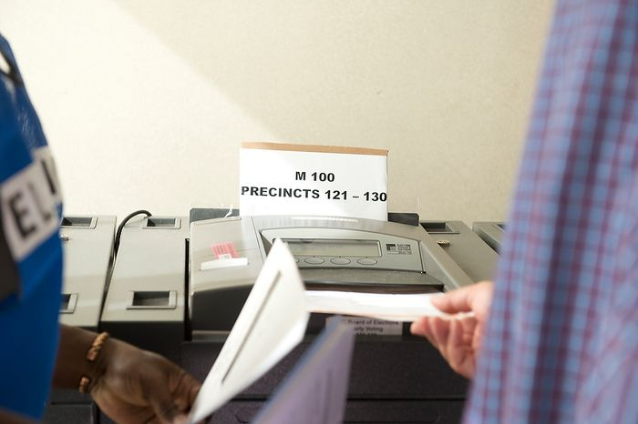 A voter slides a paper ballot into one of the voting machines at Judiciary Square in Washington on Wednesday, Oct. 24, 2012. According to voter site officials, some 2,400 voters had voted here since Monday, when the early voting opened. (Barbara L. Salisbury/The Washington Times)