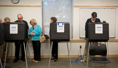 Election board representatives, including supervisor Richard Schmitt (third from left), test a voting machine with a woman who disputed her vote, saying the machine cast a blank ballot because of machine error, at the Dolley Madison Library in McLean, Va., on Wednesday, Oct. 24, 2012. (Barbara L. Salisbury/The Washington Times)