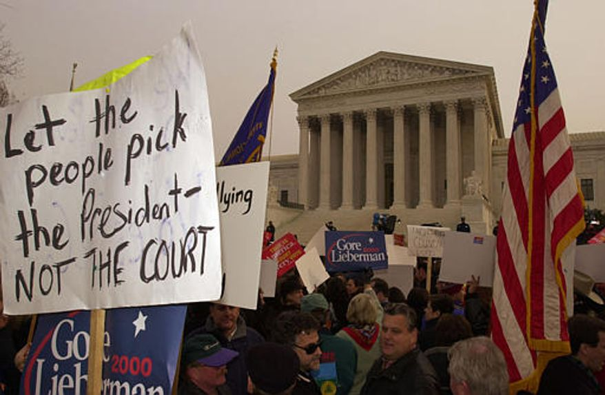 Protesters hold signs and flags in front of the U.S. Supreme Court in Washington on Monday, Dec. 11, 2000. The court will hear arguments on an appeal by Texas Gov. George W. Bush, the Republican presidential candidate, to stop the hand recount of presidential ballots in Florida. The court ordered the recount stopped on Saturday. (AP Photo/Steve Helber)