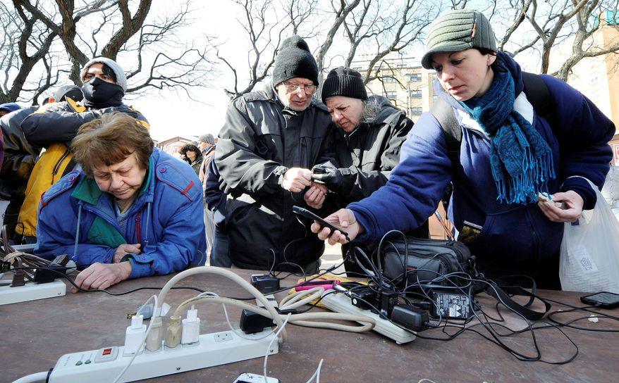 Long Beach, N.Y. residents (from the left) Claudia Brass, Nicholas and Xenia Moulinos and Kimberly Chenkin charge their cellphones at a Verizon charging station in front of city hall on Tuesday. Another storm is headed their way, but it is expected to be less powerful than originally predicted. (Associated Press)