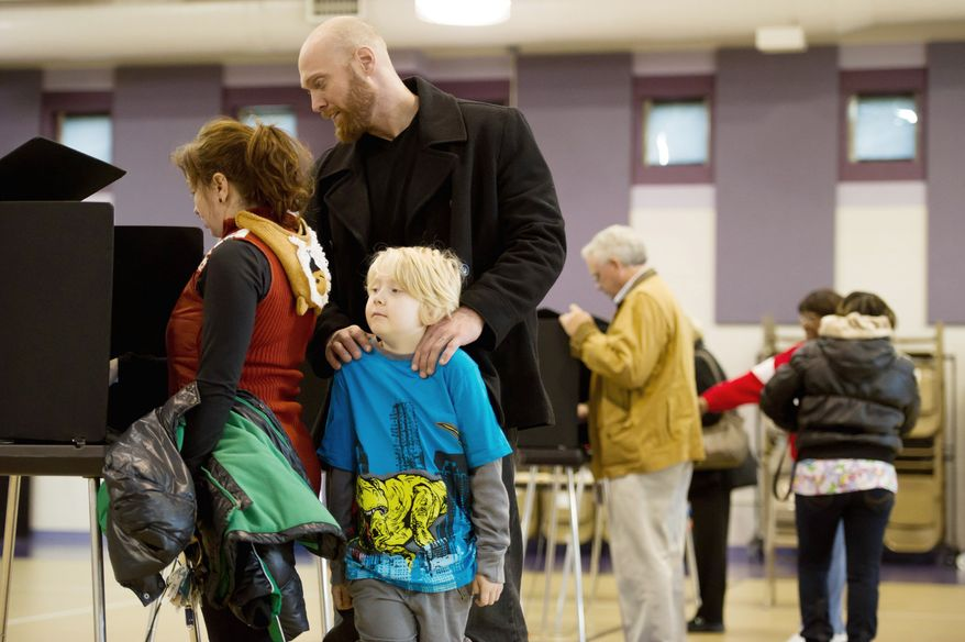Rob Weaver and his son Ben Magnvs, 7, waits for Jessica Weaver as she finishes voting at Linwood Holton Elementary School on election day morning, Richmond, Va., Tuesday, November 6, 2012. (Andrew Harnik/The Washington Times)