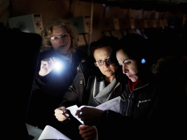Poll workers Eva Prenga (right), Roxanne Blancero (center) and Carole Sevchuk try to start an optical-scanner voting machine in the cold and dark at a polling station in a tent in the Midland Beach section of Staten Island, N.Y. on Tuesday morning. The original polling site, a school, was damaged by the storm last week. (Associated Press)