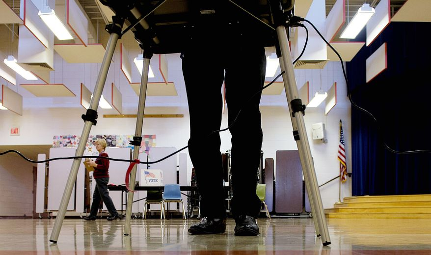 A voter casts his ballot Tuesday at Grantsville Elementary School in Grantsville, Md. At Ridgecrest Elementary in Hyattsville, a crowd lines up to enter the polls. While less publicized than referendums on gambling and same-sex marriage, an Election Day vote on the Dream Act in Maryland still was a contentious issue at the ballot box. (Barbara L. Salisbury/The Washington Times)