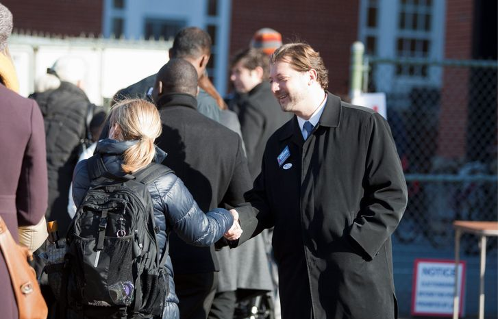 David Grosso (left), running for an at-large D.C. Council seat, greets a voter at a Precinct 33 polling site Tuesday. The Democrat was given the best chance for an upset. Incumbent at-large D.C. Council member Michael A. Brown (below), a Democrat, makes a last campaign pitch to voters outside a Precinct 110 polling site Tuesday. There were five challengers for his and another at-large seat.