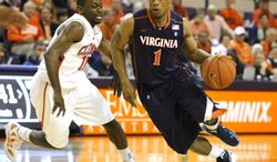 Virginia's Jontel Evans (1) drives past Clemson's Andre Young (11) during the first half of an NCAA college basketball game on Tuesday, Feb. 14, 2012, in Clemson, S.C. Clemson won 60-48. (AP Photo/Rainier Ehrhardt)