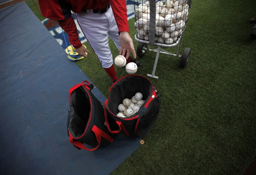 A member of the Washington Nationals drops baseballs into a bag before Game 3 of the National League division baseball series against the St. Louis Cardinals on Wednesday, Oct. 10, 2012, in Washington. (AP Photo/Pablo Martinez Monsivais)