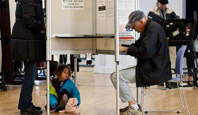 A child waits under the voting booth while her mom cast her vote at Janney Elementary School, precinct 30, Washington, D.C., Tuesday, Nov. 6, 2012 (Craig Bisacre/The Washington Times) ** FILE **
