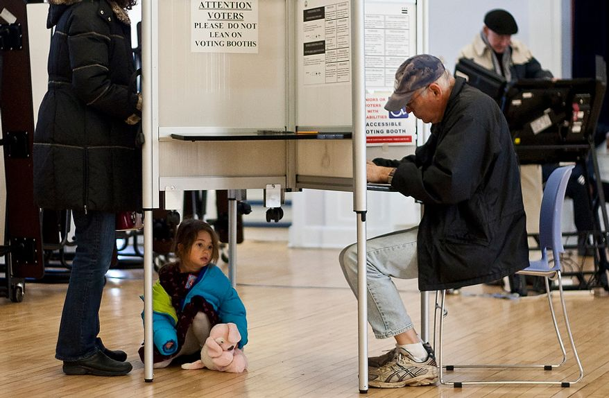 A child waits under the voting booth while her mom cast her vote at Janney Elementary School, precinct 30, Washington, D.C., Tuesday, Nov. 6, 2012 (Craig Bisacre/The Washington Times)