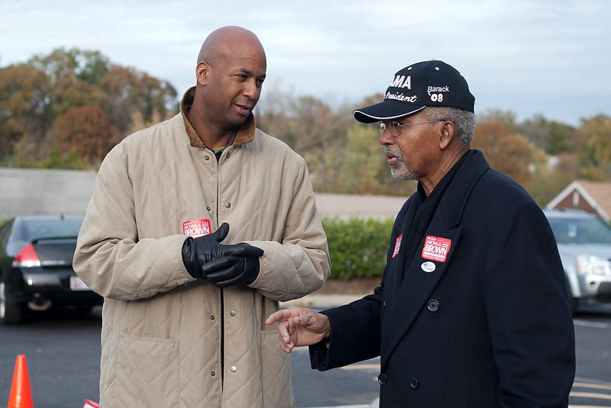 At large D.C. Council Member, Michael Brown, speaks with a volunteer outside of precinct 110 polling site in Washington, D.C., to cast their vote, Tuesday, Nov. 6, 2012 (Craig Bisacre/The Washington Times)