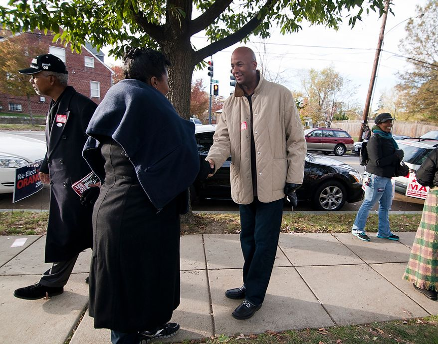 At large D.C. Council Member, Michael Brown, right, greets voters outside of precinct 110 polling site in Washington, D.C., to cast their vote, Tuesday, Nov. 6, 2012 (Craig Bisacre/The Washington Times)