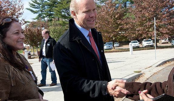 John Delaney (center), who is hoping to oust Maryland Rep. Roscoe Bartlett in Maryland's sixth district, shakes hands with voters on Election Day at Winston Churchill High School in Potomac, Md., on Nov. 6, 2012. (Barbara L. Salisbury/The Washington Times)